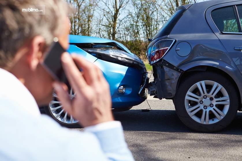 Gambar yang menunjukan seseorang yang sedang menelpon ketika mengalami kecelakaan mobil