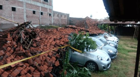 Gambar ini menunjukkan beberapa Mobil tertimpa tembok yang roboh
