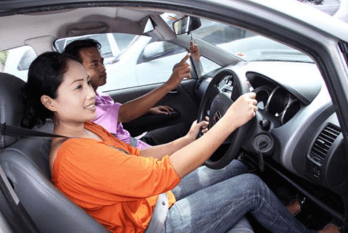Gambar ini menunjukkan 2 orang di dalam Mobil di bangku depan sedang mengemudi Mobil dan yang satu mengarahkannya