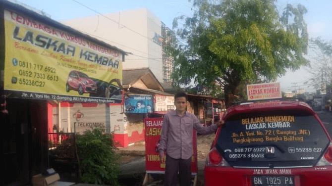 Gambar ini menunjukkan seorang pria sedang berdiri disamping Mobil warna merah di depan tempat kursus mengemudi Mobil