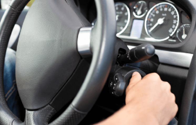 Gambar ini menunjukkan kemudi Mobil dan sebuah tangan sedang memegang anak kunci