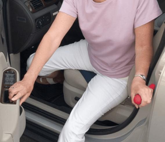 gambar ini menunjukkan seorang pengendara sedang memegang pintu untuk keluar dari Mobil