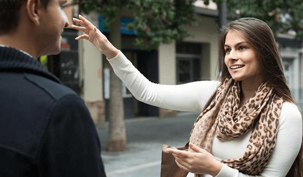 Foto seseorang sedang bertanya kepada orang lain di jalan