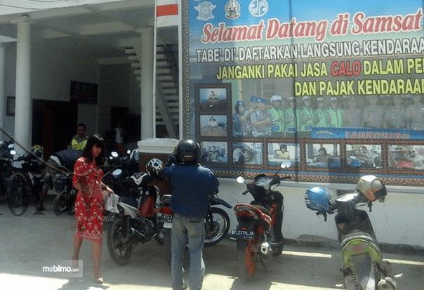 Gambar ini menunjukkan 2 orang sedang berdiri di depan kantor samsat dan terdapat banyak motor yang sedang parkir