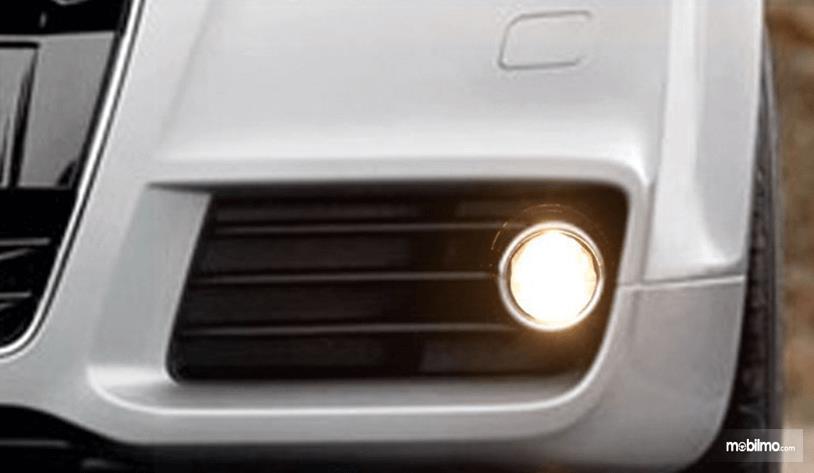 Gambar ini menunjukkan Mobil warna putih yang terlihat sebagian dengan lampu kabut menyala