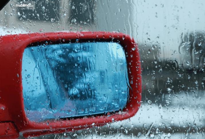 Gambar ini menunjukkan kaca spion Mobil dalam keadaan berembun saat hujan