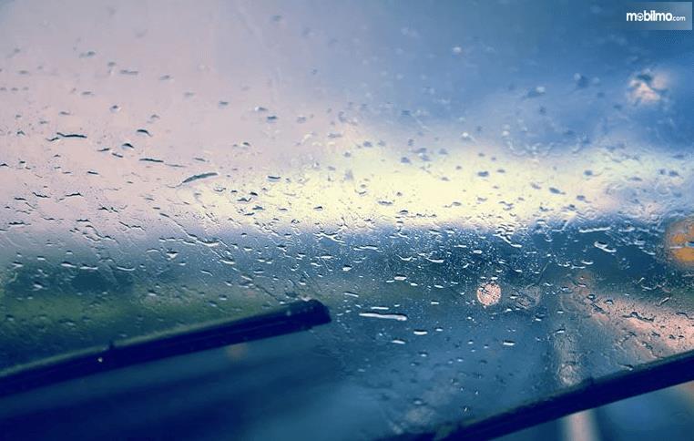Gambar ini menunjukkan embun pada kaca mobil dan terlihat wiper sedang mengusapnya