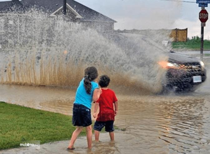 Gambar ini menunjukkan 2 orang anak sedang melihat mobil berjalan pada genangan air