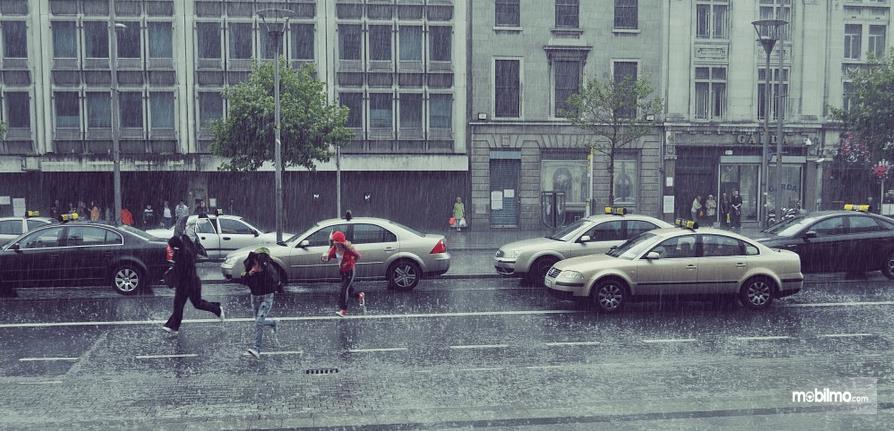Gambar ini menunjukkan beberapa orang sedang berlarian di bawah hujan dan terlihat beberapa Mobil di belakangnya