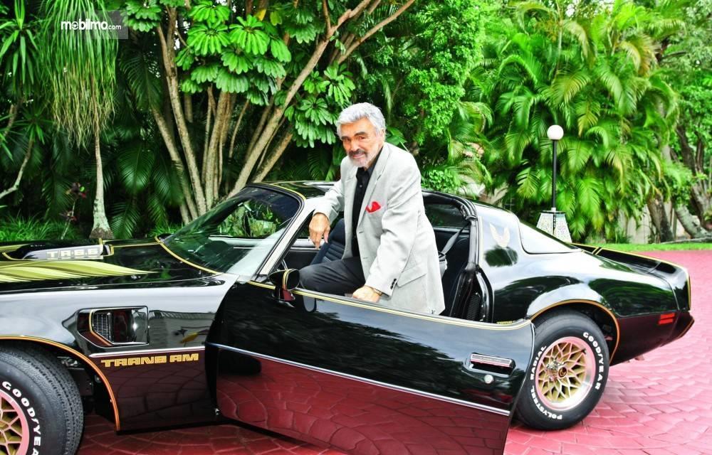 Gambar yang menunjukan Burt Reynolds berpose dengan Trans Arm