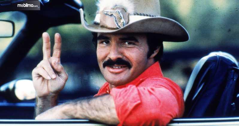 Gambar yang menunjukan Burt Reynolds berperan dalam Smoke and the Bandit