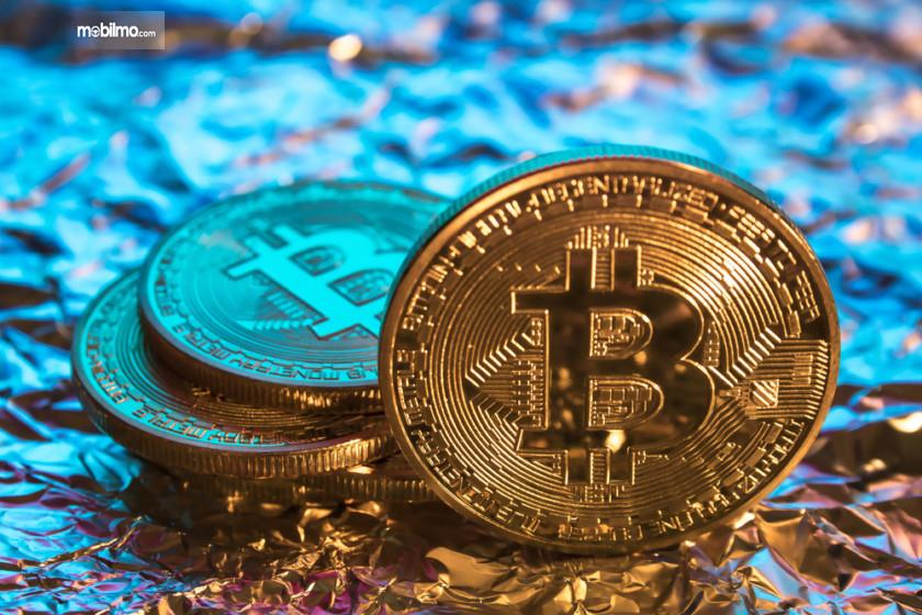 Gambar yang menunjukan koin Bitcoin dan cryptocurrency lainnya
