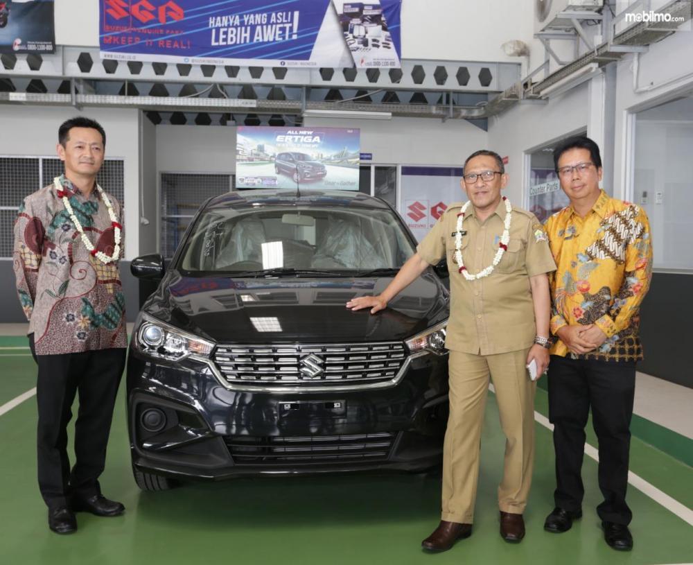 gambar menunjukan tiga orang sedang memfoto dengan mobil Suzuki Ertiga berwarna hitam