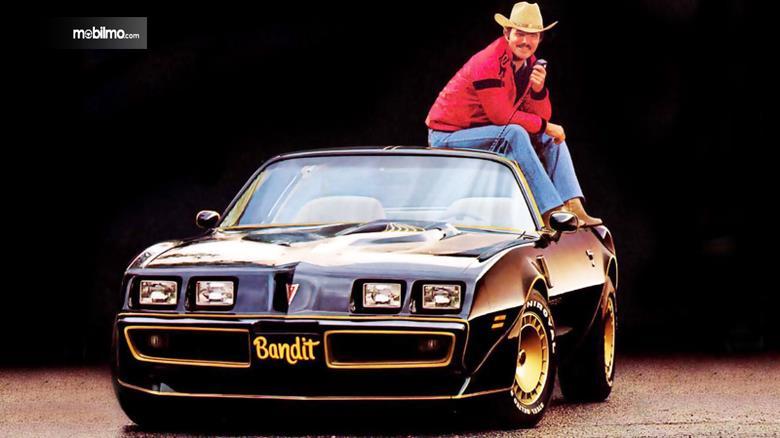 Burt Reynolds bersama dengan mobil ikoniknya dalam film Smokey and The Bandit