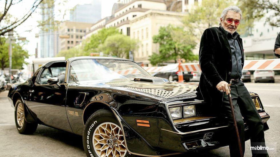 Burt Reynolds di tahun 2016 bersama mobil Pontiac Firebid Trans Arm
