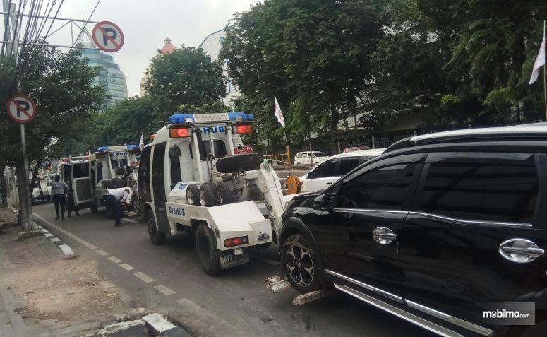 Gambar yang menunjukan kendaraan yang diangkut polisi karena parkir liar