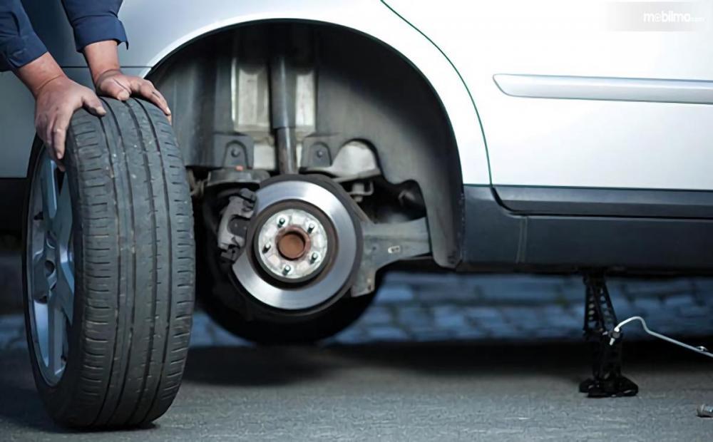 Foto seorang sedang mengganti ban mobil