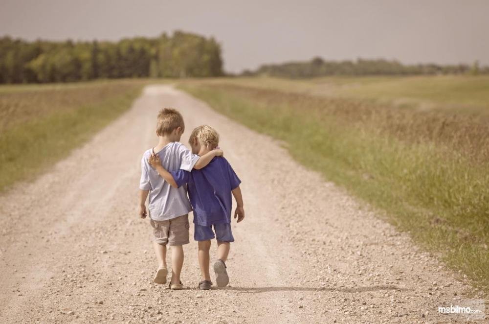 Foto dua anak berjalan berangkulan