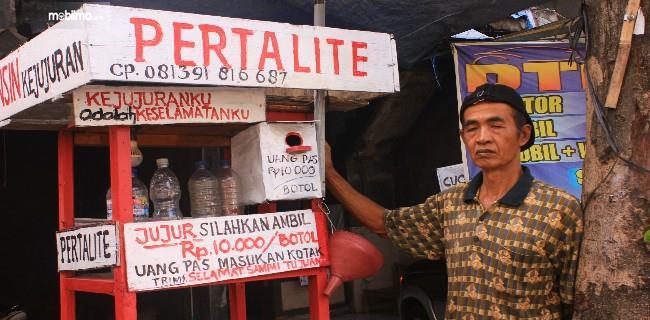 Foto Penjual bensin kejujuran bersama lapak bensinnya