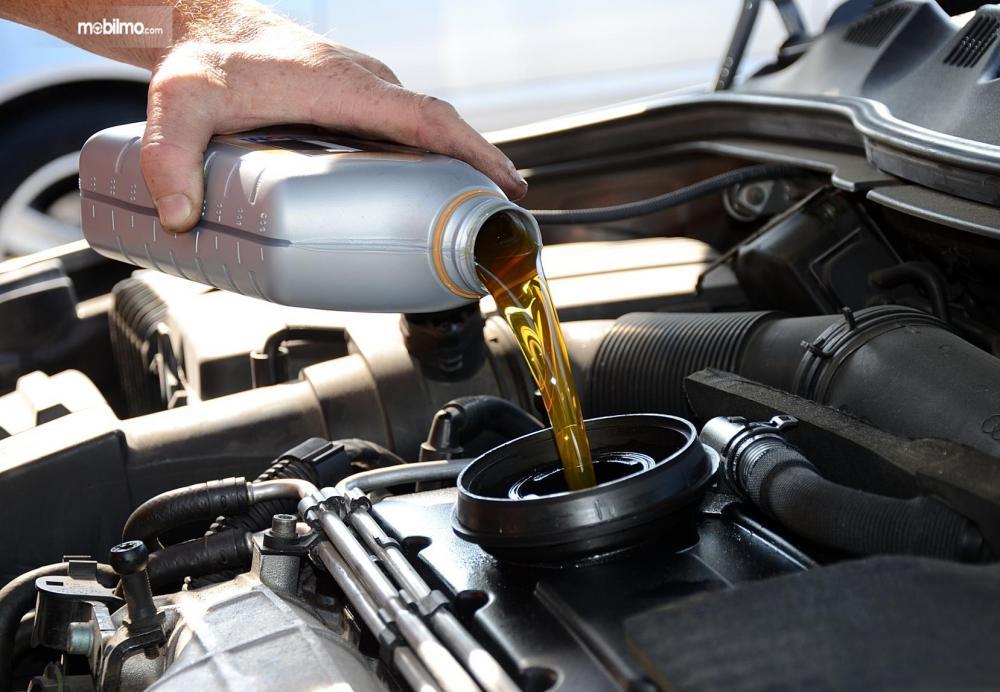 Foto seseorang sedang mengisi oli