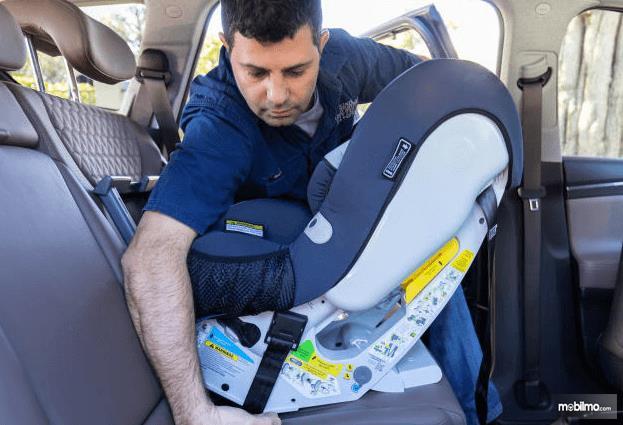 Gambar ini menunjukkan seorang pria sedang menempatkan kursi untuk anak pada bagian jok belakang