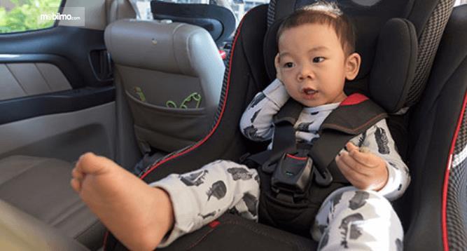 Gambar ini menunjukkan sebuah anak laki-laki sedang duduk di kursi anak menghadap ke belakang