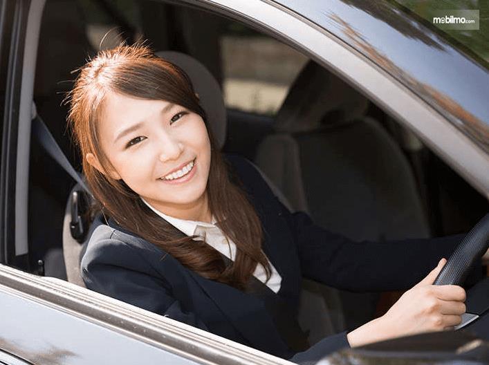 Gambar ini menunjukkan cewek cantik sedang mengemudi Mobil sambil tersenyum