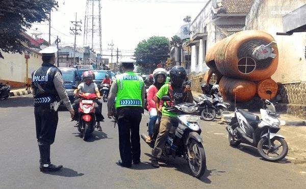 Gambar ini menunjukkan 2 orang polisi sedang berdiri di depan beberapa pengendara Motor