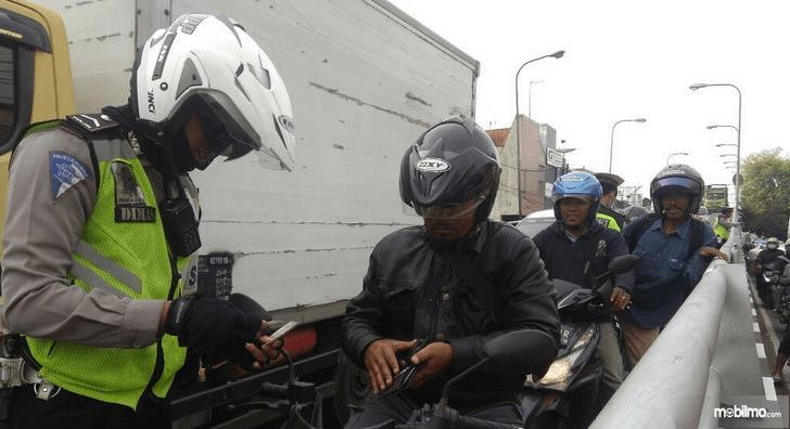 Gambar ini menunjukkan seorang polisi berdiri di depan pengendara motor disamping Mobil Box