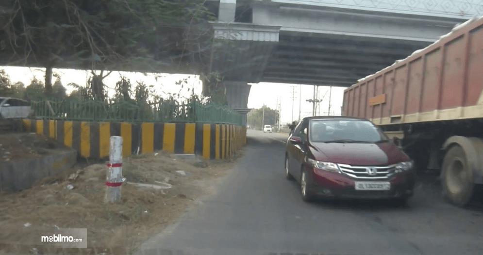 Gambar ini menunjukkan sebuah Mobil warna merah sedang menyalip truk warna merah di jalan