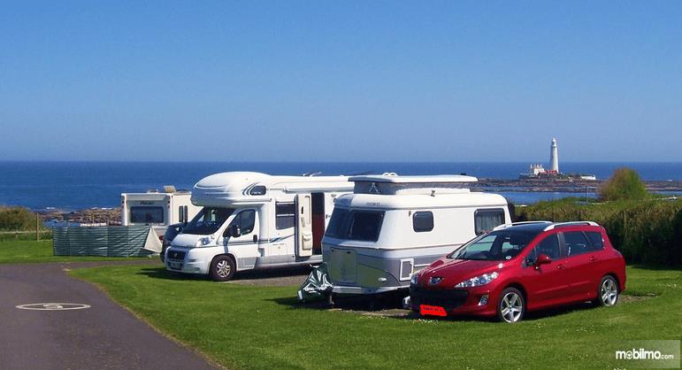 Gambar ini menunjukkan 3 Mobil dengan beda jenis dan model sedang terparkir di pinggir laut