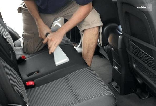 Gambar ini menunjukkan seorang pria sedang membersihkan kabin dengan vacuum cleaner