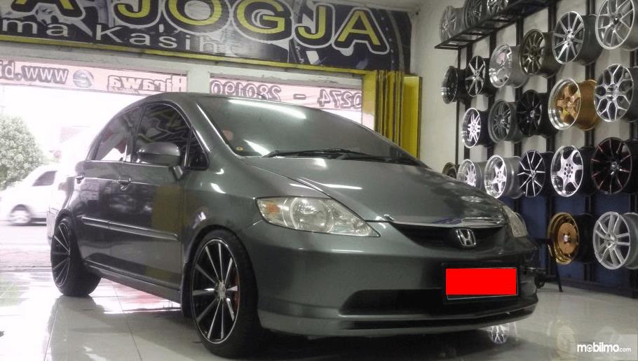 Gambar ini menunjukkan sebuah Mobil Honda warna silver sedang berada di toko velg Mobil