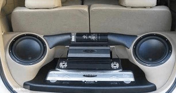 Gambar ini menunjukkan 2 subwoofer diletakkan pada bagasi Mobil di belakang kursi