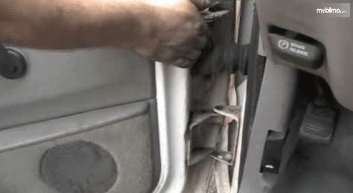 Gambar ini menunjukkan sebuah tangan memegang bagian dari pengait pintu Mobil