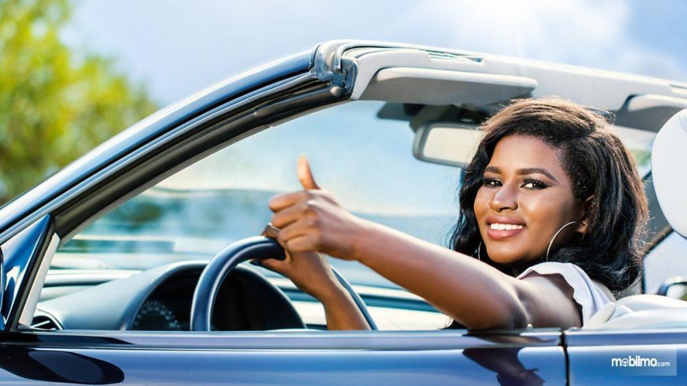 Foto Pengemudi wanita mengendarai mobilnya