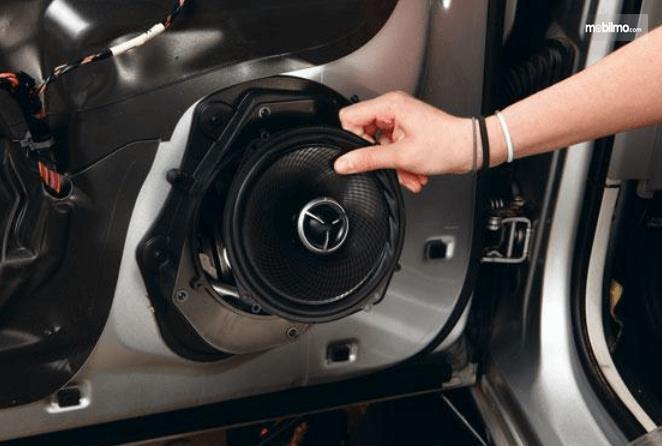 Gambar ini menunjukkan sebuah tangan memegang speaker pada Mobil