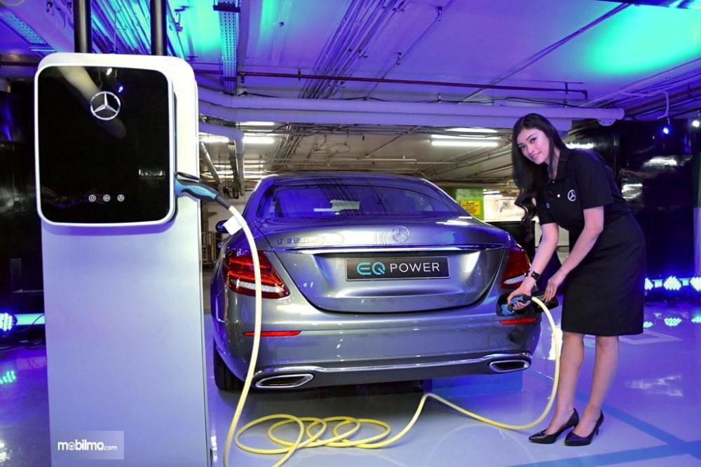 Foto seorang kru Mercedes menunjukkan bagimana cara menge-charge mobil listrik