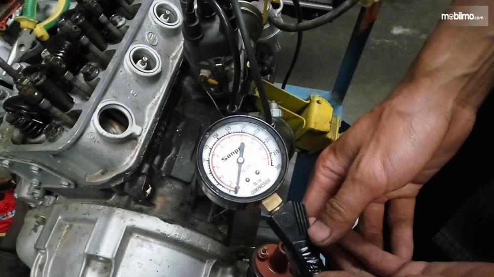 Seorang mekanik sedang mengecek kompresi pada mesin