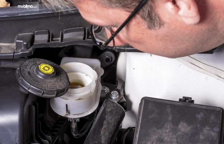 Gambar ini menunjukkan seorang pria sedang melihat volume minyak rem
