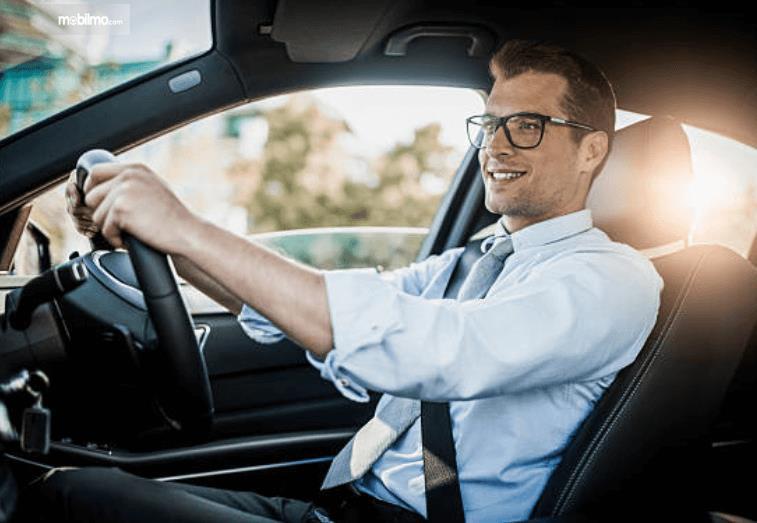 Gambar ini menunjukkan seorang pengemudi pria sambil tersenyum