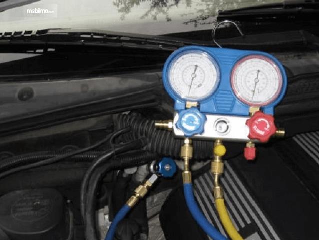 Gambar ini menunjukkan sebuah alat untuk mengisi freon AC Mobil