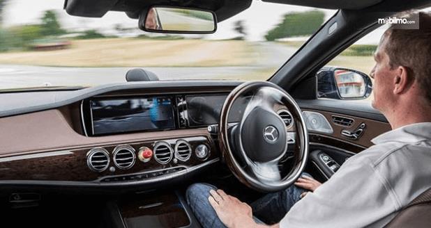 Gambar ini menunjukkan seorang pria sedang duduk di dalam Mobil