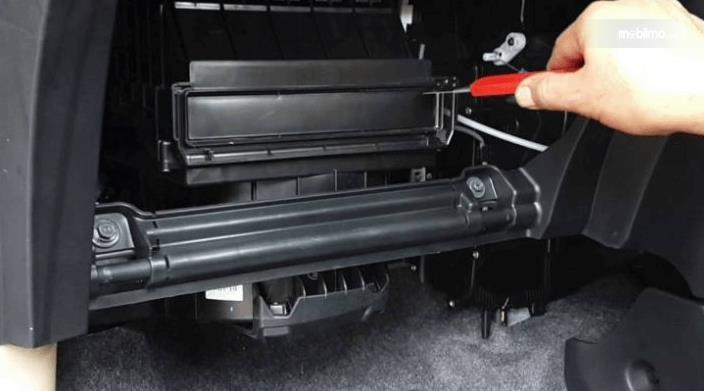 Gambar ini menunjukkan sebuah tangan sedang membuka komponen pada sistem AC Mobil