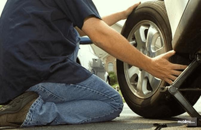 Gambar ini menunjukkan seorang pria sedang melepas ban Mobil