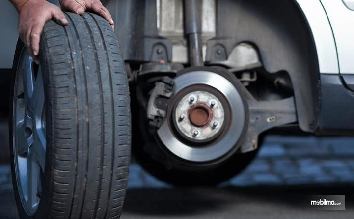 Gambar ini menunjukkan 2 buah tangan memegang roda Mobil dan terlihat di belakangnya ada poros roda