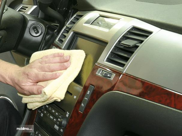 Gambar ini menunjukkan sebuah tangan memegang kanebo sedang ditempelkan pada panel dashboard Mobil