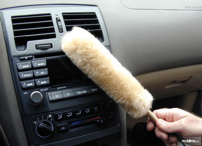 Gambar ini menunjukkan sebuah kemoceng sedang ditempelkan pada dashboard Mobil