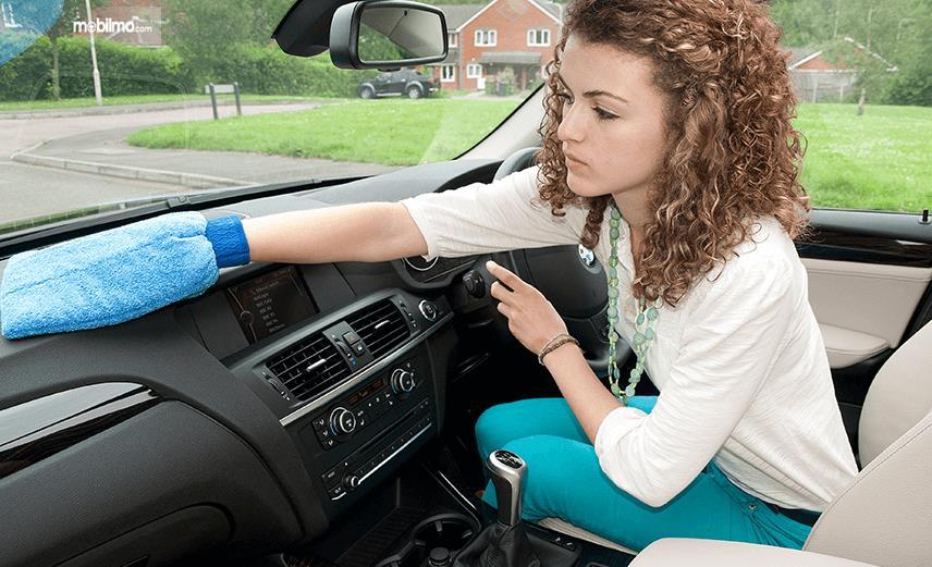 Gambar ini menunjukkan seorang wanita di dalam Mobil sedang membersihkan dashboard
