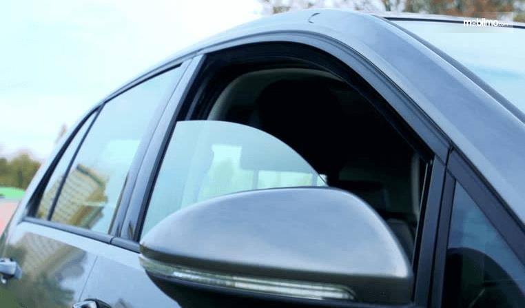 Gambar ini menunjukkan sebuah Mobil warna hitam dengan kaca jendela terbuka